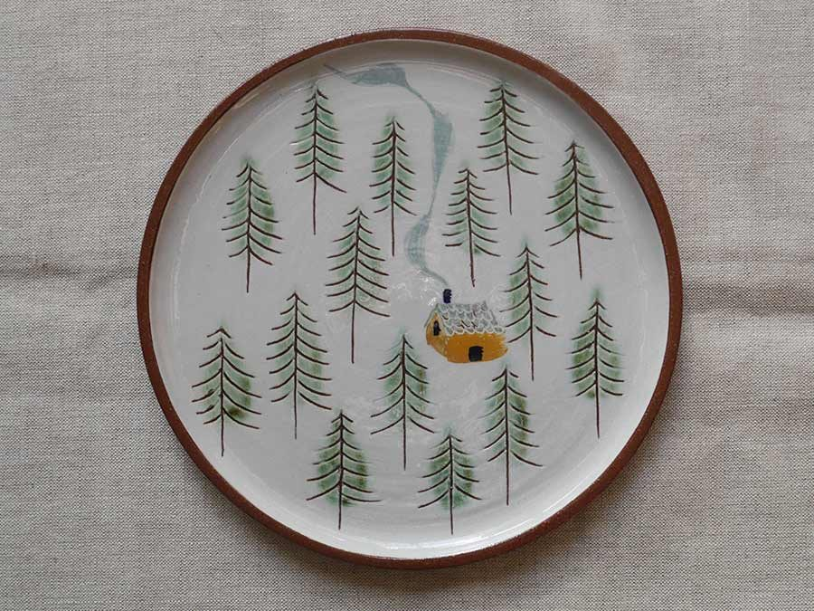 Cabin in pine forest plate
